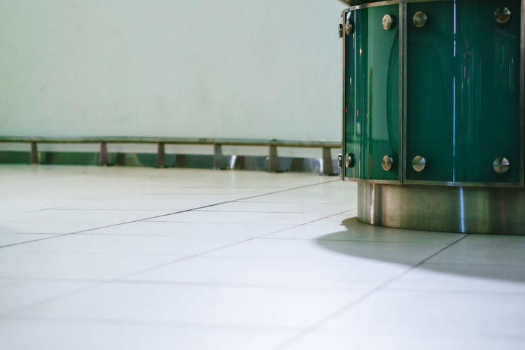 Close-up of green metal on tiled floor