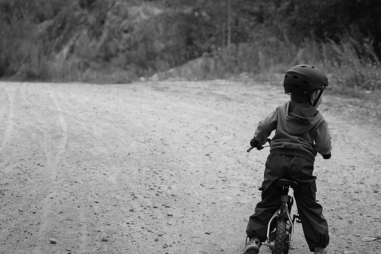 Rear view of boy riding on bicycle on road