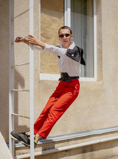 Portrait of man wearing sunglasses standing against window