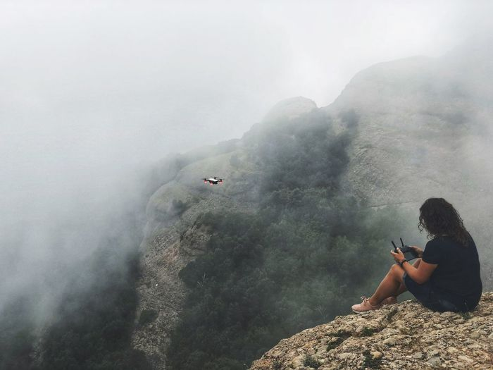 The girl sits on top of a mountain covered with the mist of a fallen cloud and controls the drone. Traveling Travel Hiking Woman Drone  Rock Formation In Clouds Clouds Cloudy Mist Mountain Peak Foggy Misty Real People One Person Leisure Activity Activity Nature Lifestyles Beauty In Nature Day Adult Land Outdoors Fog Mountain Power In Nature 17.62°