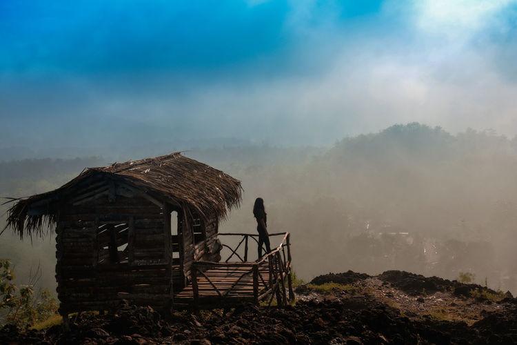Woman standing on hut at mountain peak