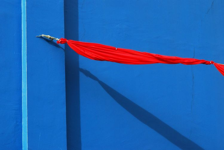 Red Cloth Tied Against Blue Wall
