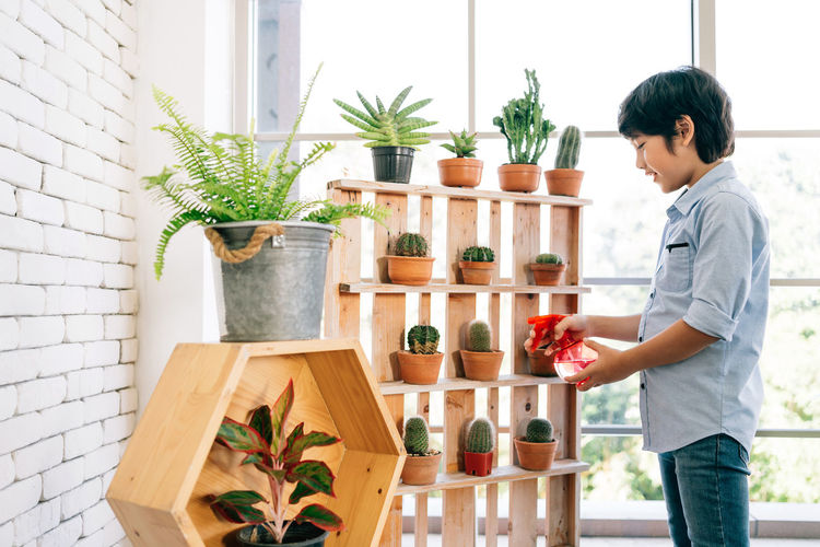 Side view of man standing by potted plants
