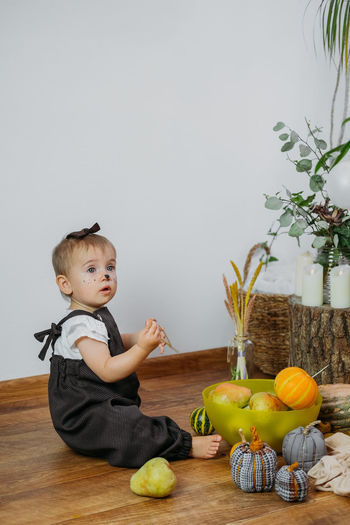 Full length of cute baby sitting on floor by pumpkins at home