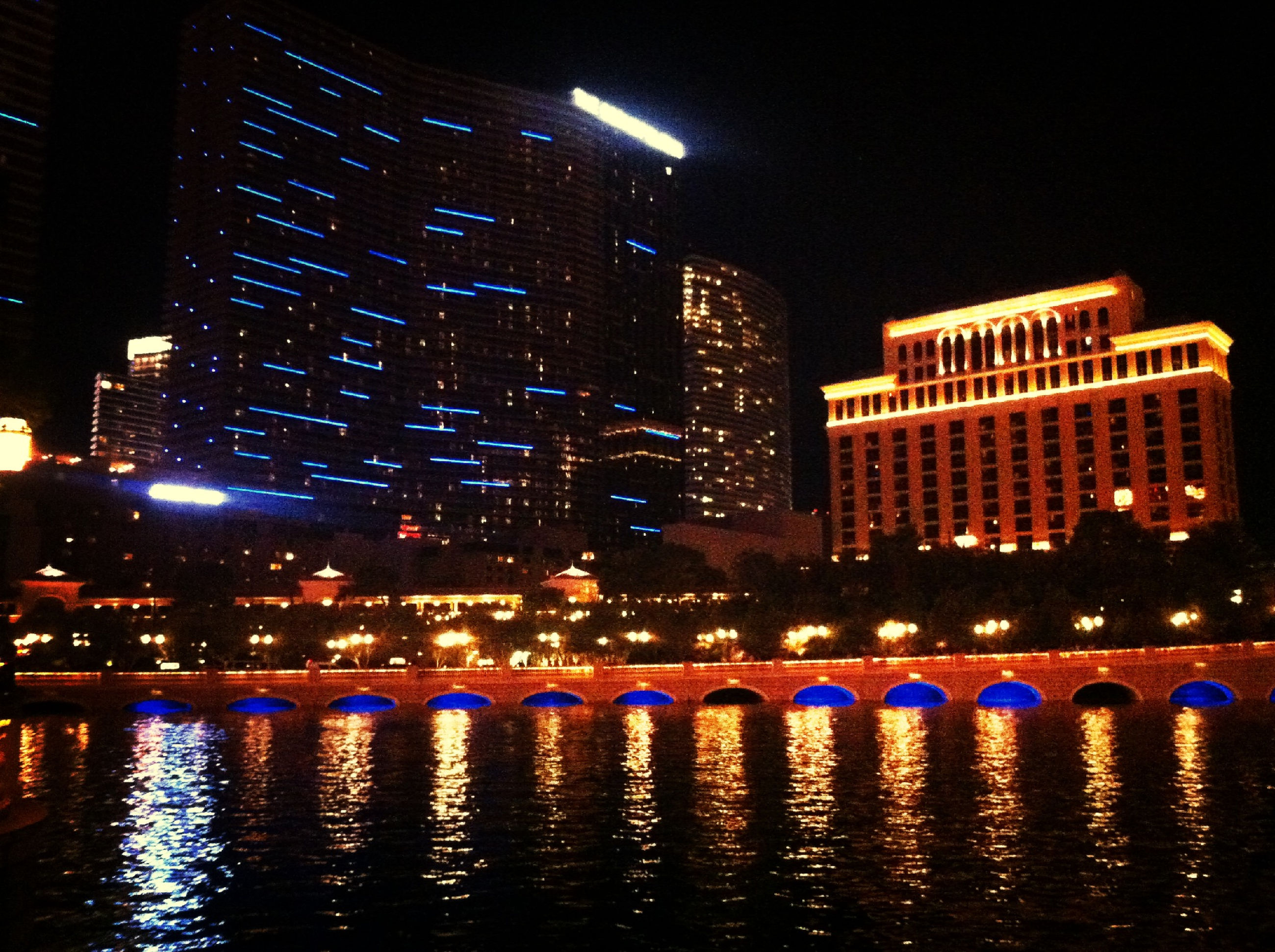 illuminated, night, building exterior, architecture, built structure, city, waterfront, water, reflection, building, skyscraper, river, office building, city life, modern, cityscape, residential building, sky, no people, outdoors