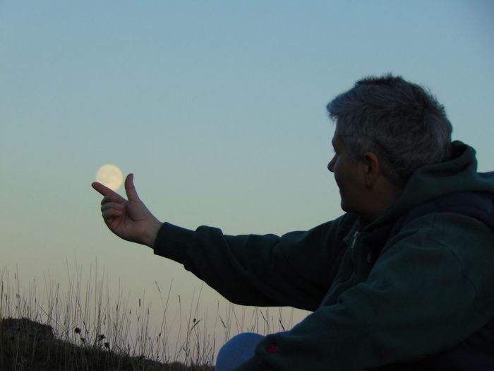 Optical illusion on man holding moon at dusk