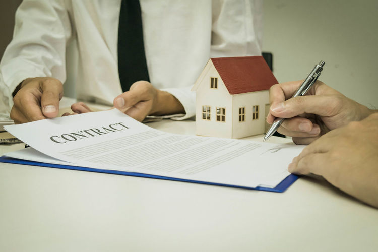 Midsection of real estate agent holding document while client signing on table
