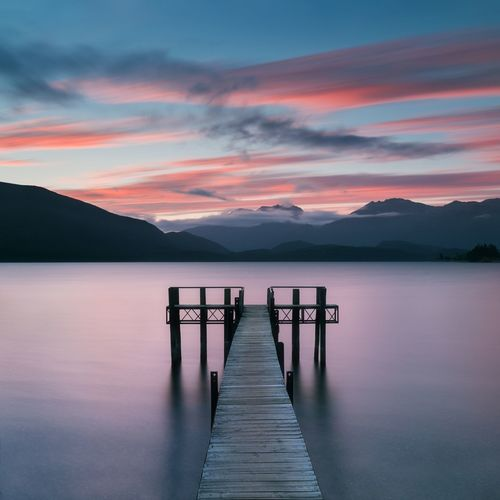 Wooden pier in lake against sky during sunset
