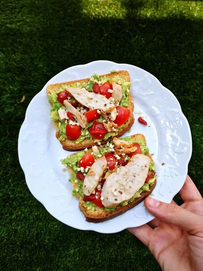 Cropped image of hand holding sandwiches in plate