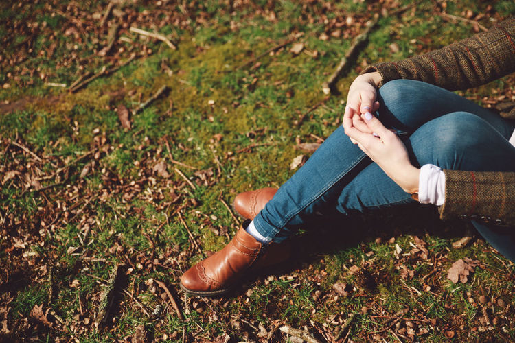 Midsection of woman sitting on field at richmond park