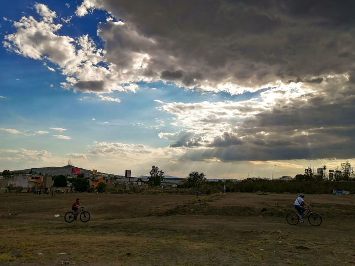 People riding bicycle on field against sky