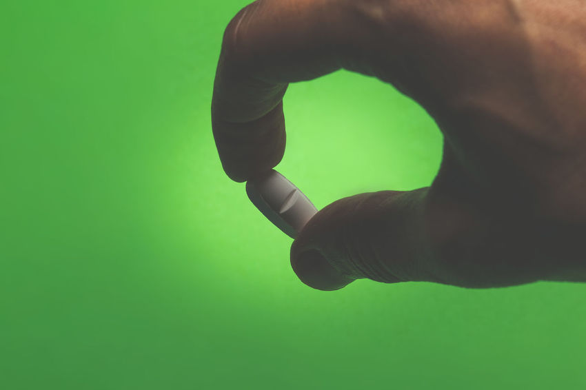 close up of a hand holding a white pill Human Body Part Human Hand Hand Body Part One Person Green Color Colored Background Green Background Studio Shot Finger Human Finger Indoors  Real People Close-up Men Lifestyles Unrecognizable Person Limb Communication Human Limb