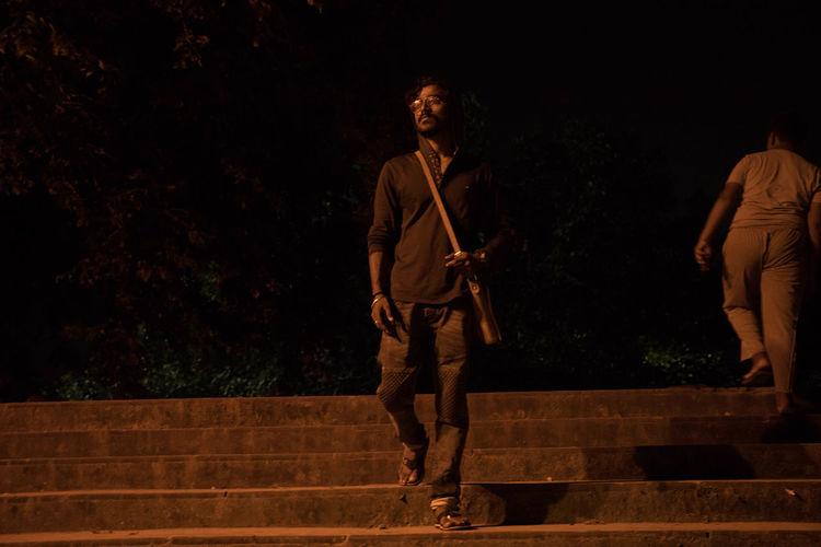 Man with umbrella walking on street at night
