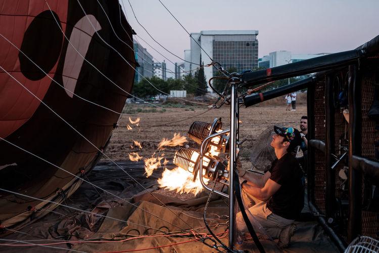 Man sitting on bonfire against built structures