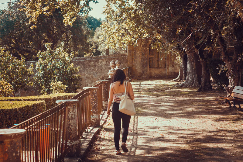 Rear view of woman standing on railing against trees