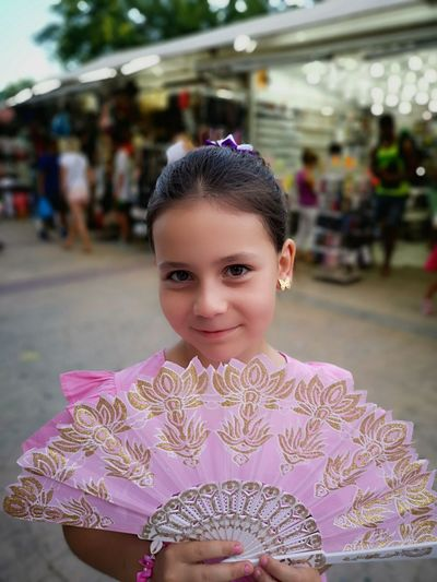 Close-Up Portrait Of Girl Holding Pink Folding Fan On Footpath