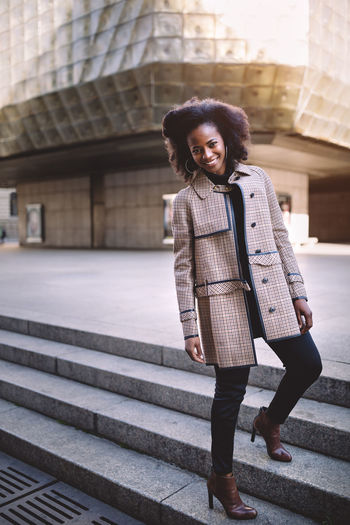 Beautiful african american young woman with afro and large hoop earrings in a stylish coat, smiling