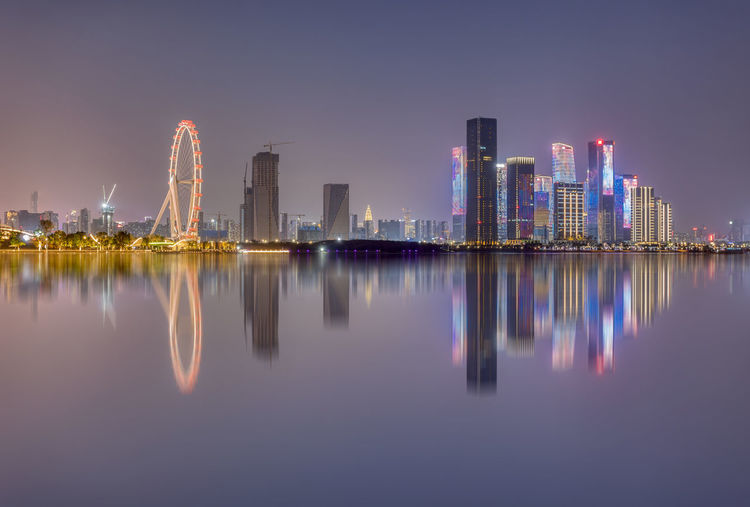 Reflection of illuminated buildings in city against sky