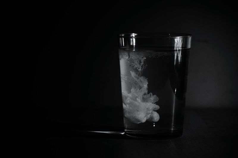 Paint with water in drinking glass against wall