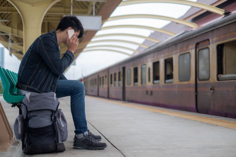 Side view of man on train at railroad station