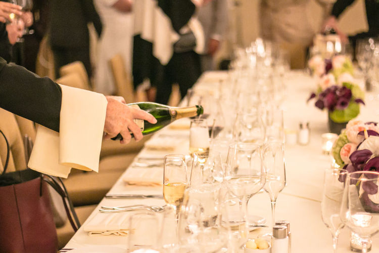 Cropped image of waiter pouring alcohol during event