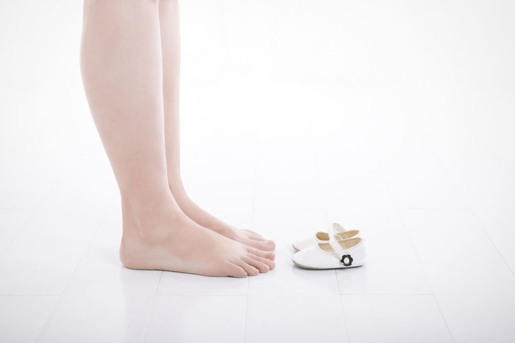 Adult feet facing a pair of baby shoes Adult Baby Baby Shoes Family Feet Future Parents High Key Human Body Part Human Leg Indoors  Low Section One Person One Woman Only Parents People White Background White Color