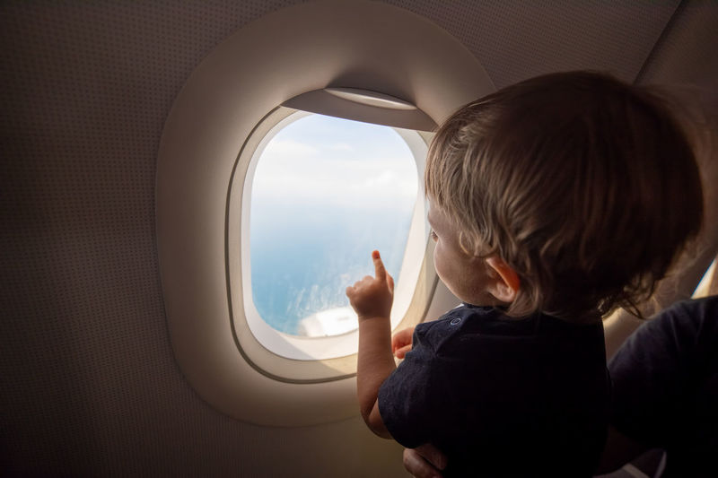 Rear view of boy looking through airplane window