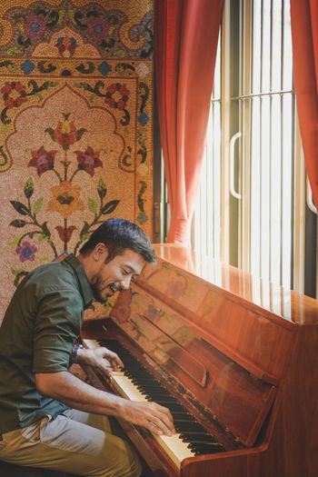 Smiling man playing piano at home