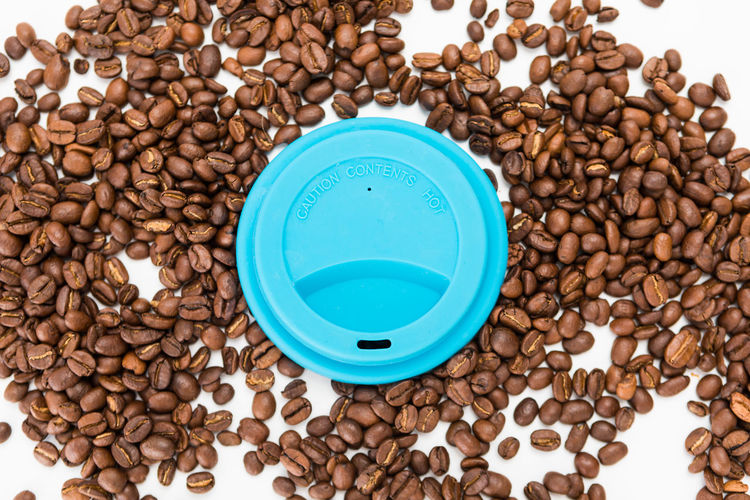Top View of Silicone Coffee Cup Lids On Coffee Beans on White Background Large Group Of Objects Coffee - Drink Abundance Coffee Roasted Coffee Bean Brown Food And Drink No People High Angle View Still Life Indoors  Food Directly Above Cup Drink Freshness Studio Shot Wellbeing Refreshment White Background Caffeine