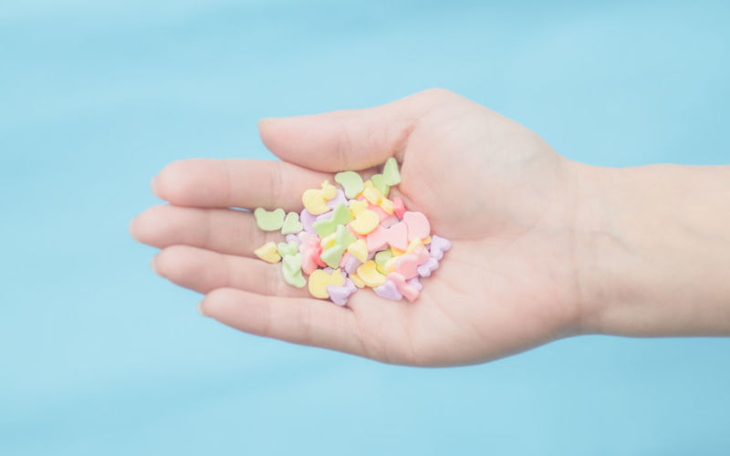Cropped Woman Hand Holding Candies Against Colored Background