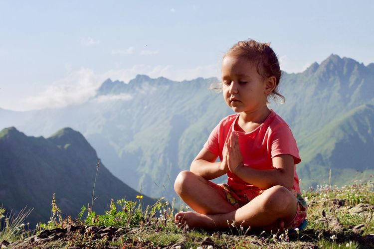 Girl Meditating While Sitting On Mountain Against Sky
