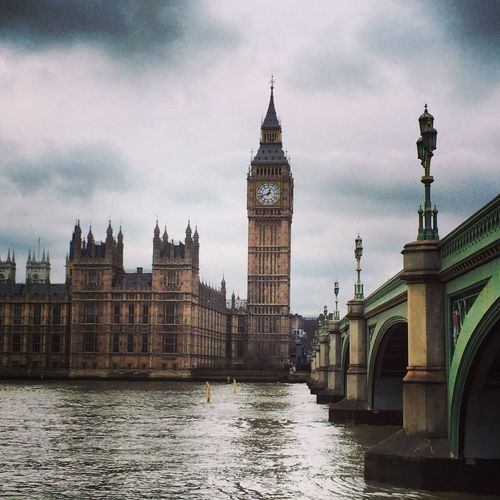 Big ben and city against cloudy sky