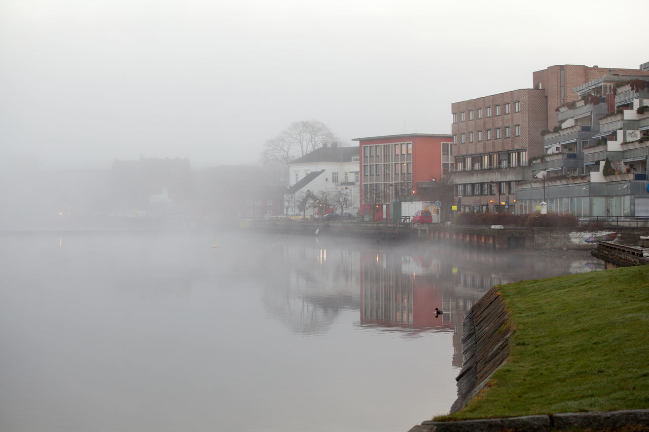 River By Buildings Against Sky During Foggy Weather