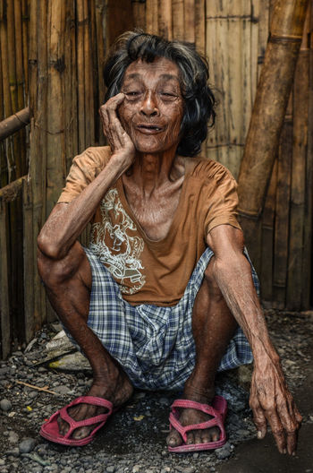 Portrait Of Homeless Senior Woman Against Wooden Wall