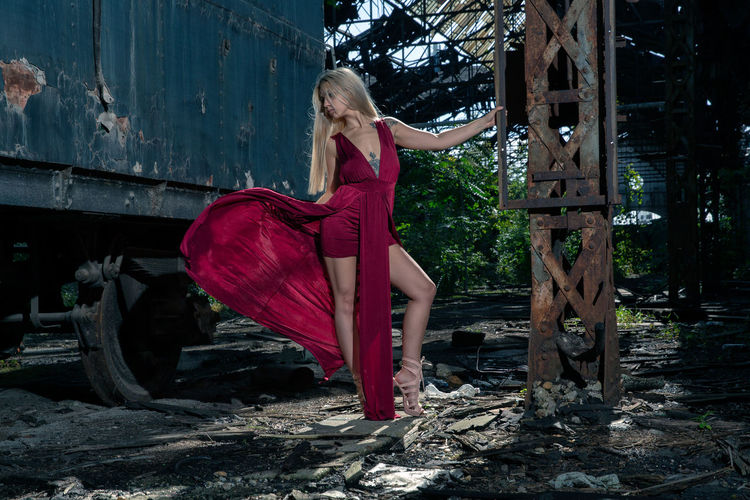 Woman standing against abandoned rusty train