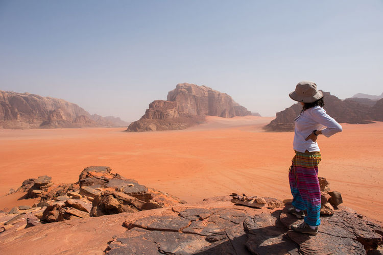 Trekker woman enjoying beautiful desert panorama on a rocky height, admiring desert landscape. Wadi Rum, Jordan. Cliffs Desert Deserts Around The World Hiking Jordan Rocky Solo Traveler! Traveling Trekking Wadi Rum Walking Around Woman Arid Arid Landscape Caucasian Desert Landscape Female Landscape Mountain Nature Sand Sand Dune Sandstone Solo Traveller Trekker