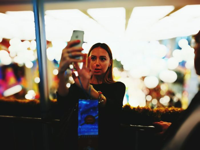 Young woman taking selfie through mobile phone while standing against illuminated lights