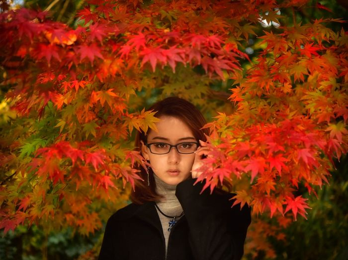 Portrait of young woman standing by plants during autumn