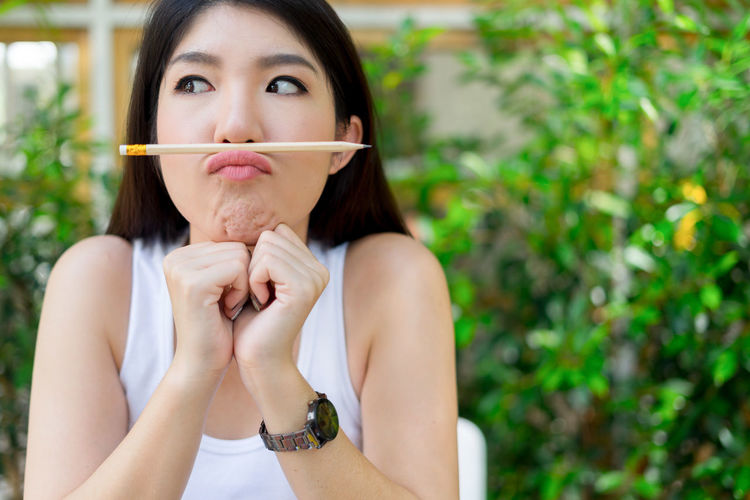 Close-Up Of Playful Young Woman Balancing Pencil On Lips