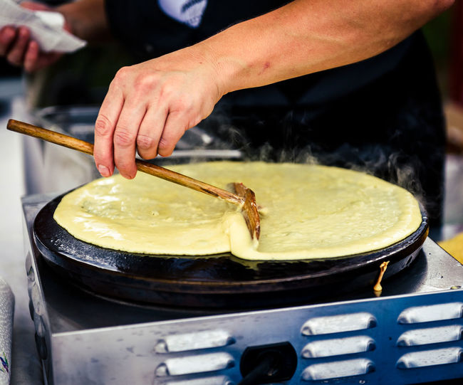 Midsection of person preparing pancake in kitchen