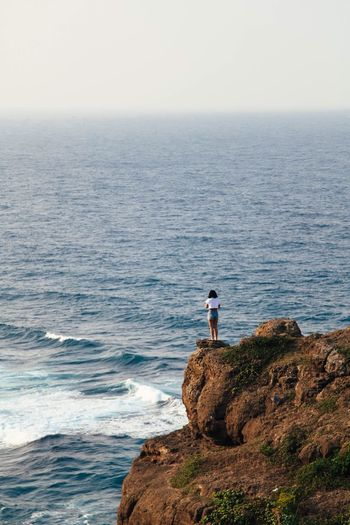 Rear view of woman standing on cliff at shore against sky