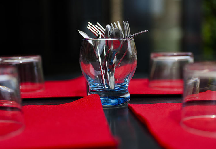 Close-up of eating utensils in glass on table