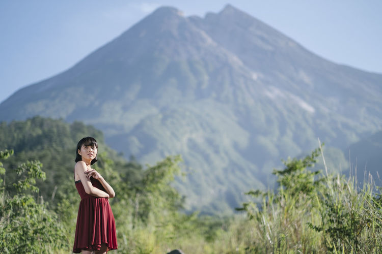 Woman looking away while standing against mountains and sky