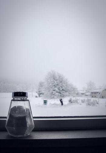 Close-up of salt shaker on window sill during winter