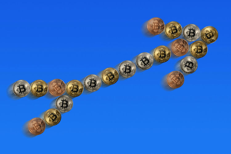 Close-up of bitcoins arranged as arrow symbol against blue background