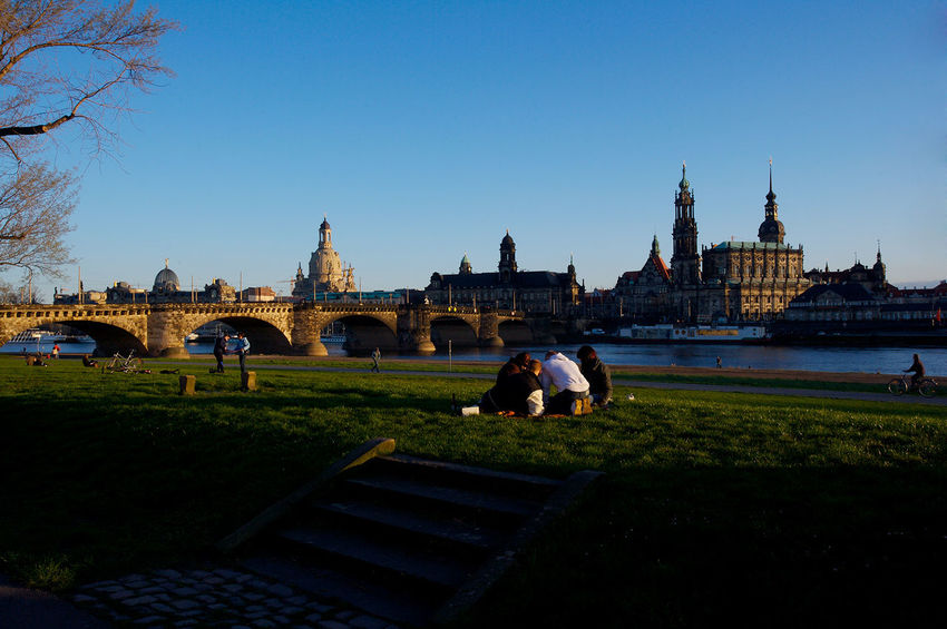 vue of the old city of Dresden by Canaletto famous painting Architecture Art Augustusbridge Blue Built Structure Carnaletto Castle City City Life Clear Sky Dresden Elbwiesen Famous Place Grass Group Of People Lawn Leisure Activity Lifestyles Outdoors People Sky Sunset Tourism Tourist Travel Destinations