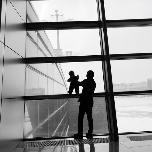 Father holding son on window frame