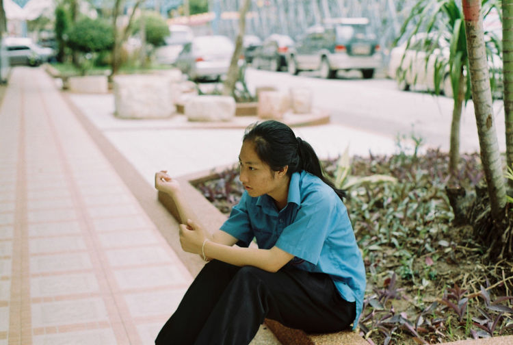 Side view of woman looking away while sitting on footpath