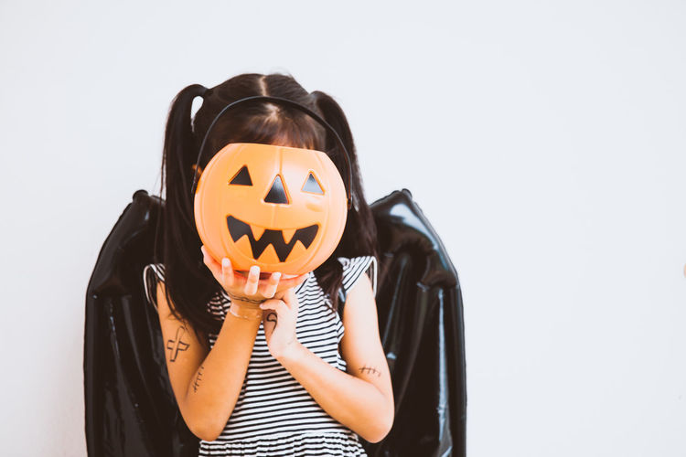 Playful girl covering face with jack o lantern bucket against wall