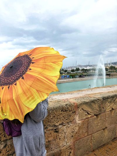 A girl is standing on a rainy day under an yellow umbrella in the form of a sunflower near an ancient stone fence against the background of a pond with a fountain and a sea port Travel Destinations Tourist Traveling Travel Waterfront Yellow Fountain Rainy Sunflower Umbrella Woman Girl Water Cloud - Sky Sky Sea Real People Land Day Lifestyles People Women Leisure Activity Outdoors Unrecognizable Person Spraying